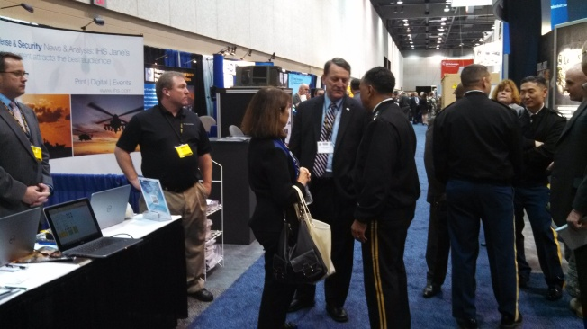 Four Star General Dennis Via, Commander of the US Army Materiel Command (center right) and Major General (Ret) Freeman from Deloitte (center) visit the ProModel booth and discuss the positive impact that DST-SM is having on the Army Materiel Command.